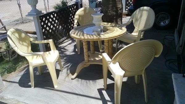 Mesa de madera con cuatro sillas de plastico